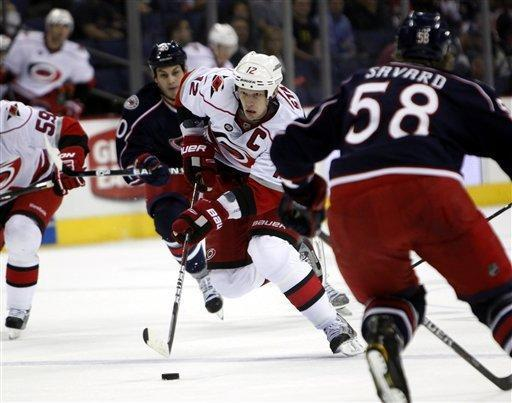 Carolina Hurricanes' Eric Staal (12) skates with the puck between Columbus Blue Jackets' Jared Boll (40) and David Savard (58) during the first period of an NHL hockey game on Friday, March 23, 2012, in Columbus, Ohio. (AP Photo/Terry Gilliam)