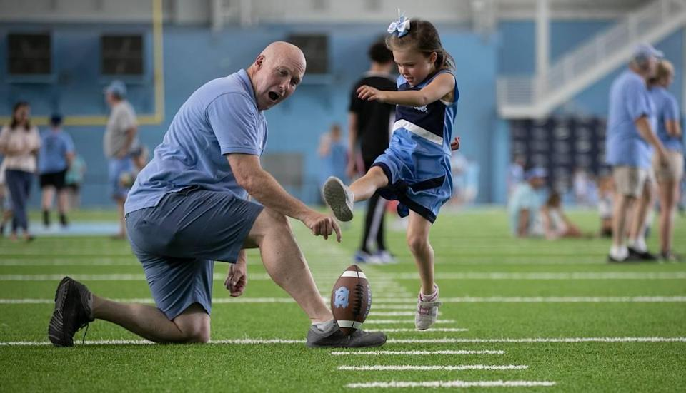 Tim Tompkins of Raleigh, N.C. acts as a place holder for his six-year-old daughter Arabella Tompkins as she practices her field goal kicking form during the annual Meet The Heels event on Saturday, August 3, 2019 at the Football Practice Complex in Chapel Hill, N.C.