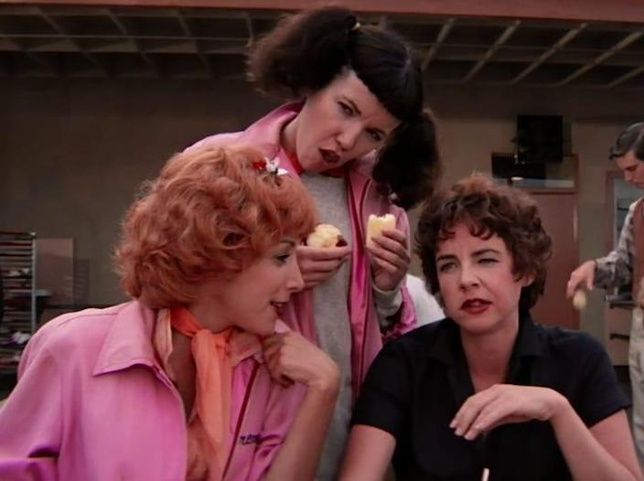 the pink ladies sitting at a picnic table outside school