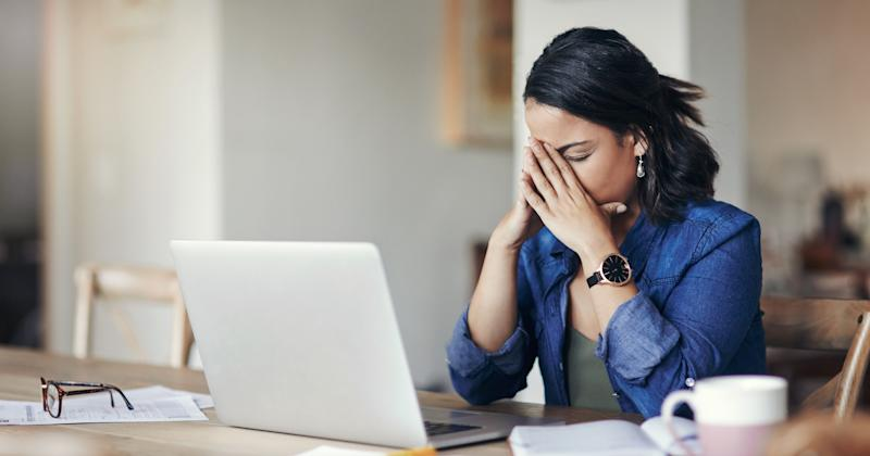 A woman looking stressed while using a laptop at home.