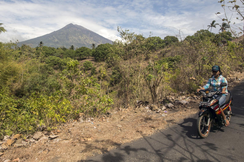 A villager rides past by with Mount Agung seen in the background in Karangasem, Bali, Indonesia, Sunday, Sept. 24, 2017. Thousands of villagers on the Indonesian resort island have been evacuated to temporary shelters amid fear that Mount Agung will erupt for the first time in more than half a century. Its last eruption in 1963 killed 1,100 people. (AP Photo/J.P. Christo)