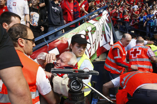 An Osasuna supporter is helped by assistant after one fence of the stadium was broken while people celebrated a goal of their team, during their last Spanish League soccer match between Osasuna and Betis,, at El Sadar stadium, in Pamplona northern Spain, Sunday, May 18, 2014. (AP Photo)