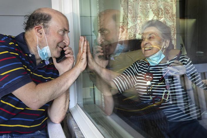 A man and his mother raise their palms to each other from opposite sides of a window while talking on cellphones