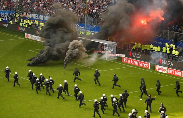 Soccer Football - Bundesliga - Hamburger SV v Borussia Moenchengladbach - Volksparkstadion, Hamburg, Germany - May 12, 2018 Hamburg fans let off flares and throw smoke bombs on to the pitch as riot police run across the pitch REUTERS/Morris Mac Matzen DFL RULES TO LIMIT THE ONLINE USAGE DURING MATCH TIME TO 15 PICTURES PER GAME. IMAGE SEQUENCES TO SIMULATE VIDEO IS NOT ALLOWED AT ANY TIME. FOR FURTHER QUERIES PLEASE CONTACT DFL DIRECTLY AT + 49 69 650050