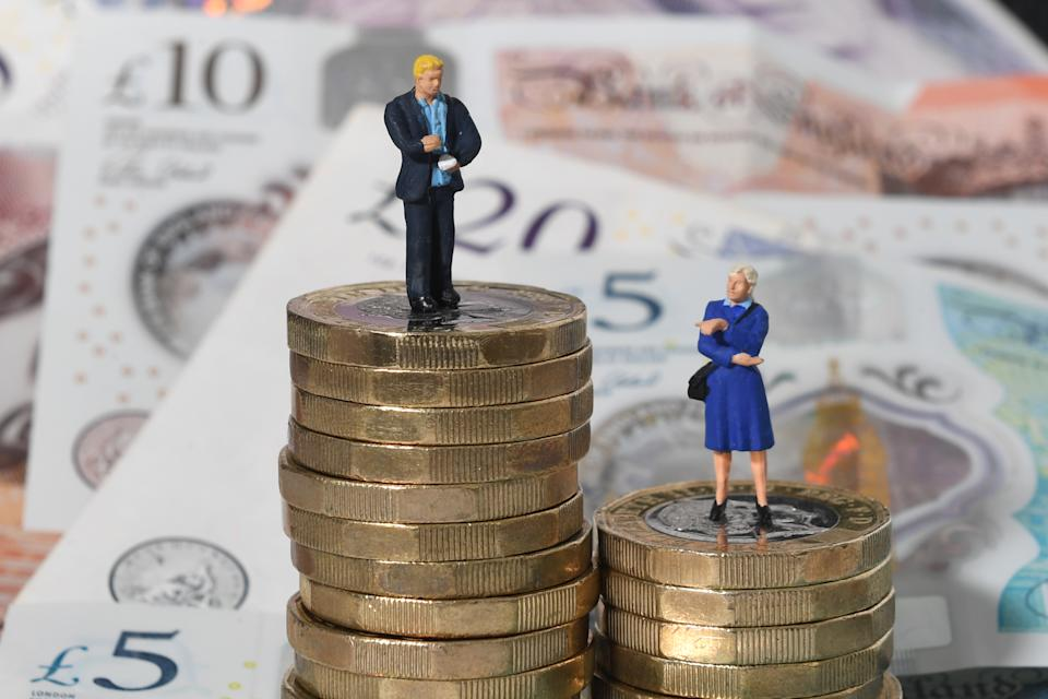 Models of a man and woman stand on a pile of coins and bank notes.