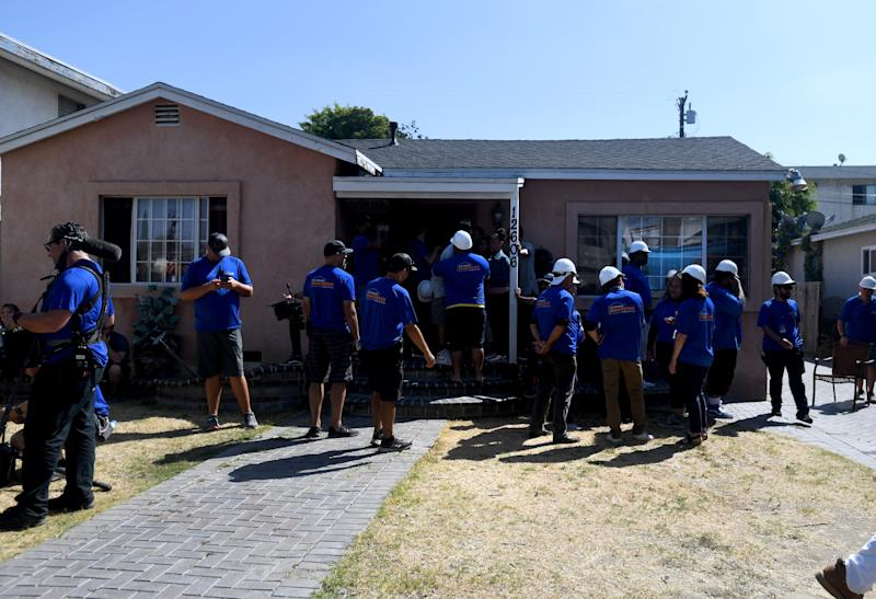 The cast and crew of Extreme Makeover: Home Edition arriving at a house which will be renovated on one of the episodes.