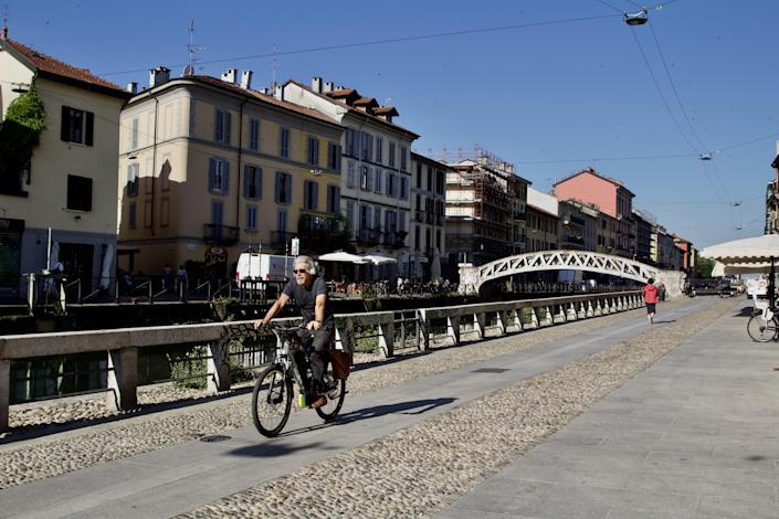 Cyclist rides along the canal in Navigli district (Joey Tyson)