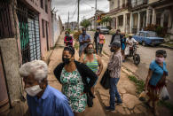 Yuliet Colon, center in tank top, waits her turn outside an agricultural market in Havana, Cuba, Friday, April 2, 2021. Colon is among several Cubans who, with more ingenuity than resources, help their compatriots cope with shortages exacerbated by the new coronavirus pandemic with Facebook posts of culinary creations designed around what they're actually likely to find at the market or with government rations. (AP Photo/Ramon Espinosa)