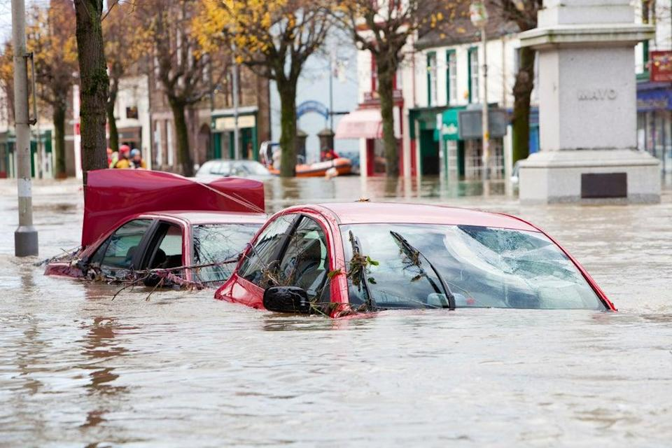 The climate crisis makes extreme weather events, such as heatwaves, hurricanes and floods, both more likely and more frequent. Here, flooded cars are pictured on Cockermouth Main Street (Global Warming Images/WWF)