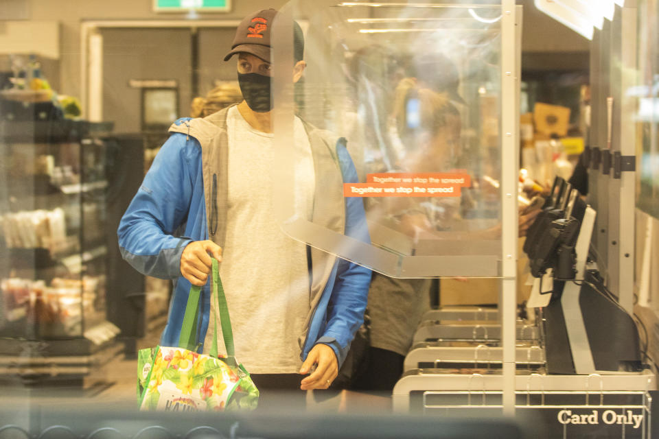 SYDNEY, AUSTRALIA - JANUARY 03: Shoppers are seen at a partitioned  supermarket checkout at The Corso in Manly on January 03, 2021 in Sydney, Australia. Face masks are now compulsory in certain indoor settings across NSW as the state continues to record new COVID-19 cases in the community. As of midnight, face masks are mandatory on public transport, in retail shops and supermarkets, indoor entertainment including cinemas and theaters, places of worship and hair and beauty premises. Face masks are also mandatory for all staff in hospitality venues and casinos and for patrons using gaming services. Stay at home lockdown orders for residents in the southern zone of the Northern Beaches have now been lifted, with the area now subject to the same restrictions as Greater Sydney, while the northern Northern Beaches area remains under lockdown until 9 January.  (Photo by Jenny Evans/Getty Images)