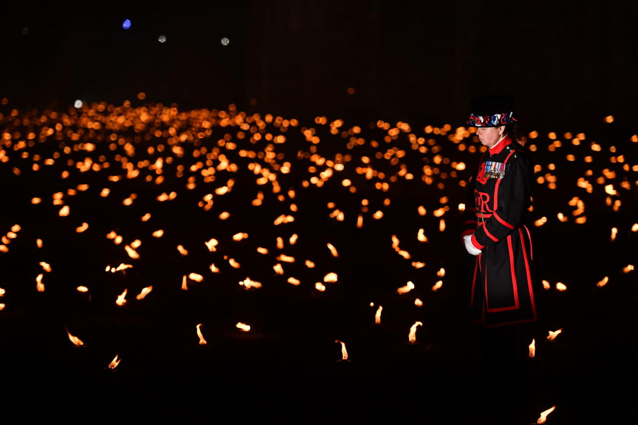 <p>A Yeoman Warder, commonly referred to as a 'Beefeater', stands amongst the first of thousands of lit flames which form part of an installation called 'Beyond the Deepening Shadow: The Tower Remembers', in the dry moat of the Tower of London, to mark the centenary of the end of World War One, Sunday Nov. 4, 2018. (Photo from John Stillwell/PA via AP) </p>