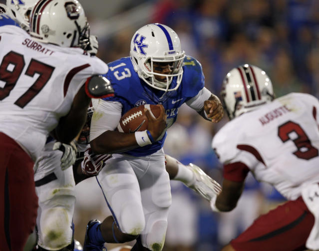 LEXINGTON, KY - SEPTEMBER 29: Jalen Whitlow #13 of the Kentucky Wildcats battles pressure from Akeem Auguste #3 and J.T. Surratt #97 of the South Carolina Gamecocks at Commonwealth Stadium on September 29, 2012 in Lexington, Kentucky. (Photo by John Sommers II/Getty Images)