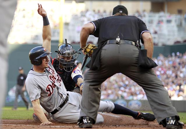 Detroit Tigers' Don Kelly (32) is tagged out by Minnesota Twins catcher Ryan Doumit, center, as home plate umpire Bob Davidson watches during the third inning of a baseball game on Saturday, June 15, 2013, in Minneapolis. (AP Photo/Genevieve Ross)