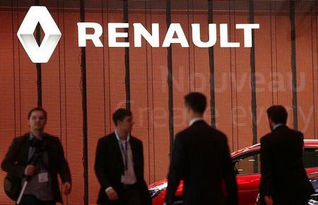 Visitors walk past a Renault logo on the car maker's booth during the second media day of the 86th International Motor Show in Geneva