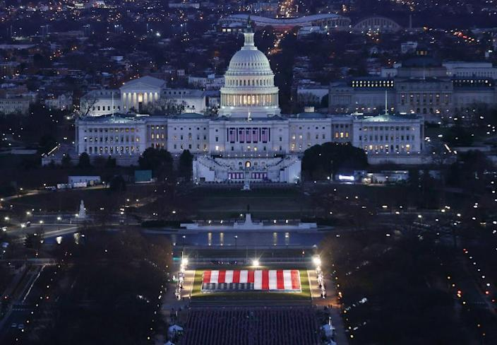 """The US Capitol Building is prepared for the inauguration ceremonies for President-elect Joe Biden as the """"Field of Flags"""" are placed on the ground on the National Mall on January 18, 2021 in Washington, DC."""
