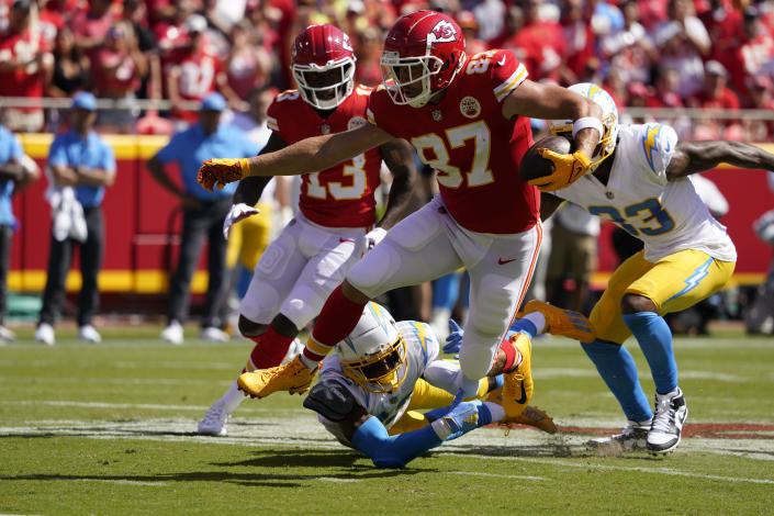 Kansas City Chiefs' Travis Kelce (87) runs out of a tackle by Los Angeles Chargers' Michael Davis (43) during the first half of an NFL football game, Sunday, Sept. 26, 2021, in Kansas City, Mo. (AP Photo/Ed Zurga)