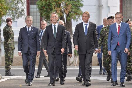 NATO Secretary-General Jens Stoltenberg and Romanian President Klaus Iohannis arrive to review NATO multinational brigade in Craiova, Romania, October 9, 2017. Inquam Photos/Bogdan Danescu/via REUTERS