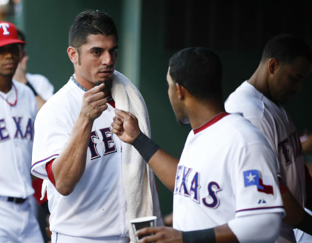 Texas Rangers starting pitcher Matt Garza, left, fist-bumps teammate Elvis Andrus, right, after pitching in the third inning of a baseball game against the New York Yankees, Wednesday, July 24, 2013, in Arlington, Texas. (AP Photo/Jim Cowsert)