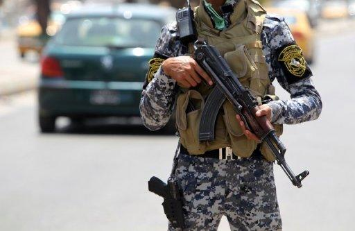 An Iraqi policeman stands guard at a checkpoint in central Baghdad