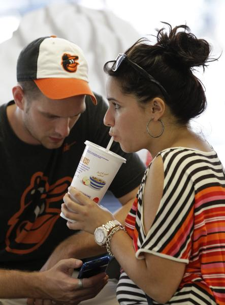 Christina Nunez, right, sips on a big soft drink as Luke Husemann checks a baseball score on his smart phone at a fast-food restaurant in New York, Thursday, Sept. 13, 2012. The era of the supersized cola may come to an end in New York City on Thursday, when health officials are expected to approve an unprecedented 16-ounce (470-milliliter) limit on sodas and other sugary drinks at restaurants, delis and movie theaters. Nunez said she orders a supersized cola every day after work. Both Husemann and Nunez are from Baltimore. (AP Photo/Kathy Willens)