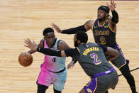 Los Angeles Lakers guard Wesley Matthews (9) and center Andre Drummond (2) defend Miami Heat guard Victor Oladipo (4), during the second half of an NBA basketball game, Thursday, April 8, 2021, in Miami. (AP Photo/Marta Lavandier)