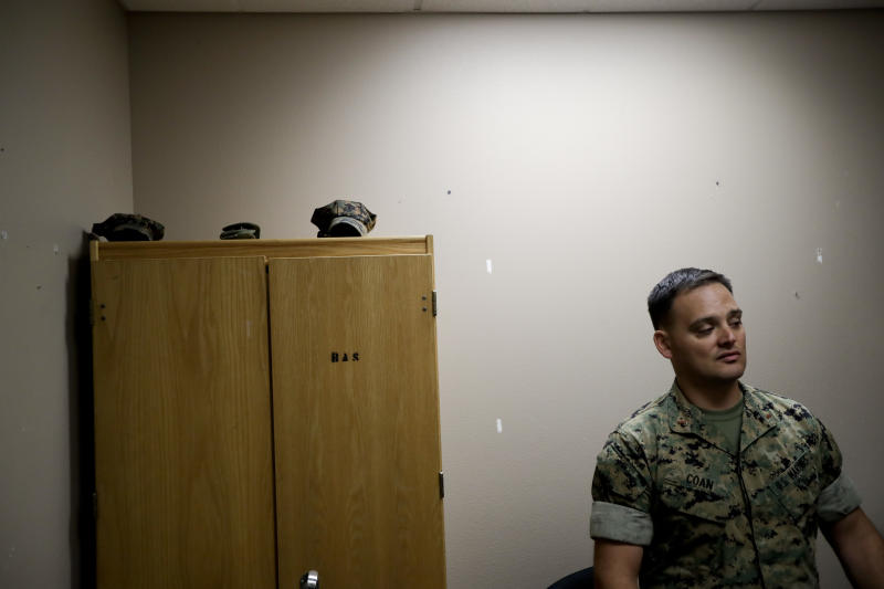 In this May 16, 2018 image, Marine Chief Warrant Officer David Coan, 35, looks out from his desk in Camp Pendleton, Calif. Coan has applied to be a part of a new cyber force after serving 17 years in the Marine Corps. The Marine Corps is considering offering bonuses to woo older, more experienced Marines to re-enlist and join its cyber operations to defend the nation, especially against cyberattacks from Russia and China. (AP Photo/Gregory Bull)