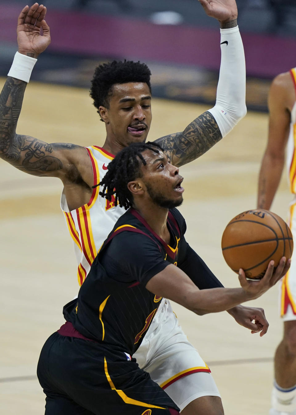 Cleveland Cavaliers' Darius Garland, front, drives to the basket against Atlanta Hawks' John Collins in the first half of an NBA basketball game, Tuesday, Feb. 23, 2021, in Cleveland. (AP Photo/Tony Dejak)