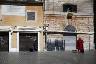 People stand in an empty street in downtown Rome, Monday, March 15, 2021. Half of Italy's regions have gone into the strictest form of lockdown in a bid to curb the latest spike in coronavirus infections that have brought COVID-19 hospital admissions beyond manageable thresholds. (Cecilia Fabiano/LaPresse via AP)