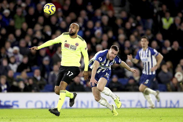 Sheffield United's David McGoldrick (left) and Brighton and Hove Albion's Adam Webster battle for the ball, during their English Premier League soccer match against Brighton & Hove Albion at the AMEX Stadium, Brighton, England, Saturday, Dec. 21, 2019. (Gareth Fuller/PA via AP)