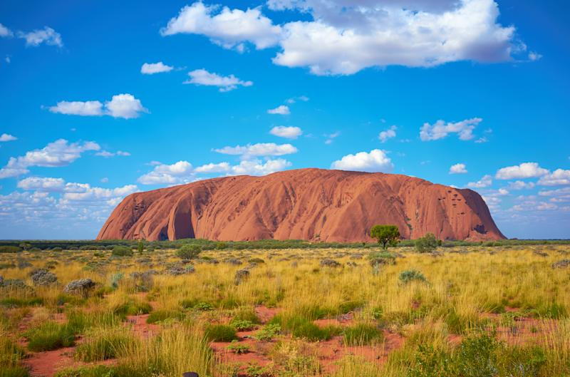 Uluru, Northern Territory, Australia - May 19, 2011: Fluffy clouds drift over Uluru (also known as Ayers Rock) in the Australian Outback. A genuine Wonder of the Natural World (and a UNESCO World Heritage Site), it's also a sacred place to the local Anangu people.
