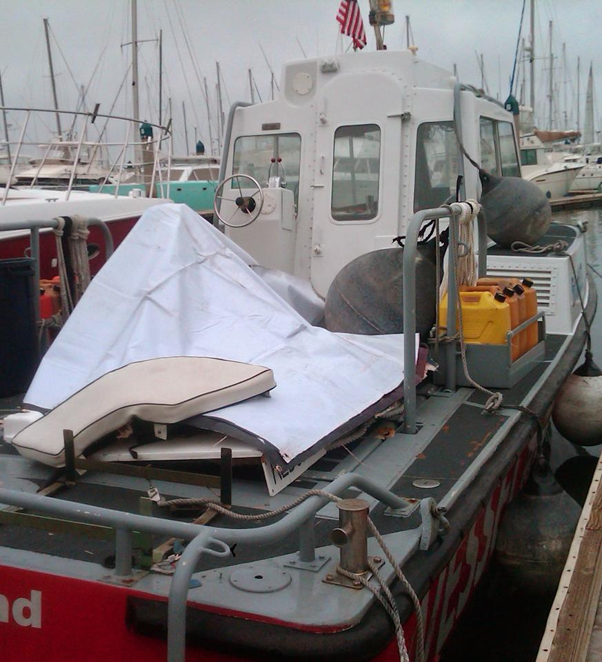 A white seat cushion is seen on a white tarp covering wreckage recovered from a yacht that collided with a larger vessel, on a boat used for a rescue search in Ensenada, Baja California, Mexico, Sunday, April 29, 2012. The 37-foot Aegean, carrying a crew of four, was reported missing Saturday, the U.S. Coast Guard said. The yacht appeared to have collided at night with a much larger vessel, leaving three crew members dead and one missing,(AP Photo/Elliot Spagat)