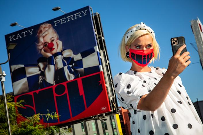 "Pop star Katy Perry, in a mask that says ""smile,"" takes a selfie with a billboard of herself wearing a red clown nose."