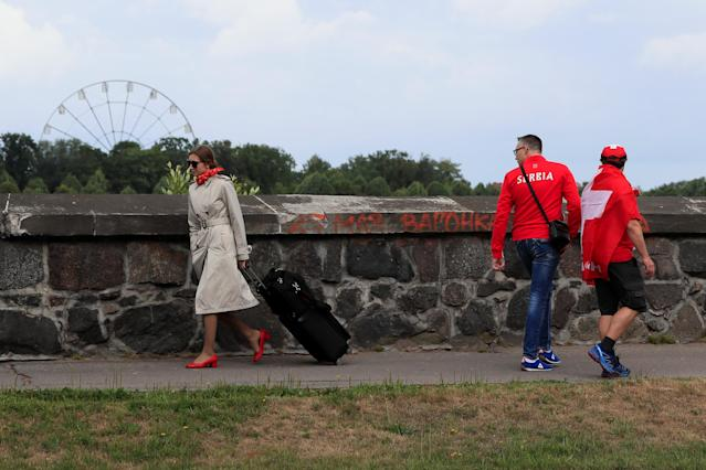 A Switzerland fan and a Serbia fan walk next to a flight attendant in Kaliningrad, Russia, June 22, 2018. As well as shooting all the matches, Reuters photographers are producing pictures showing their own quirky view from the sidelines of the World Cup. Picture taken June 22, 2018. REUTERS/Gonzalo Fuentes