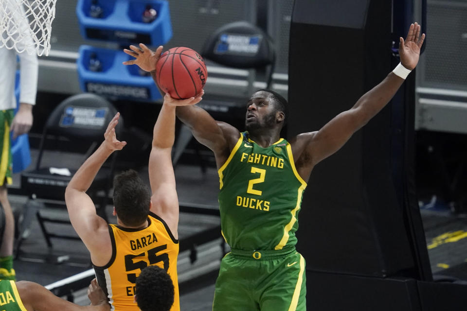 Iowa's Luka Garza (55) has his shot blocked by Oregon's Eugene Omoruyi (2) during the first half of a second-round game in the NCAA men's college basketball tournament at Bankers Life Fieldhouse, Monday, March 22, 2021, in Indianapolis. (AP Photo/Darron Cummings)