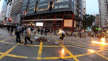 Flames by a molotov cocktail can been seen on a journalist during a protest in Wan Chai, Hong Kong