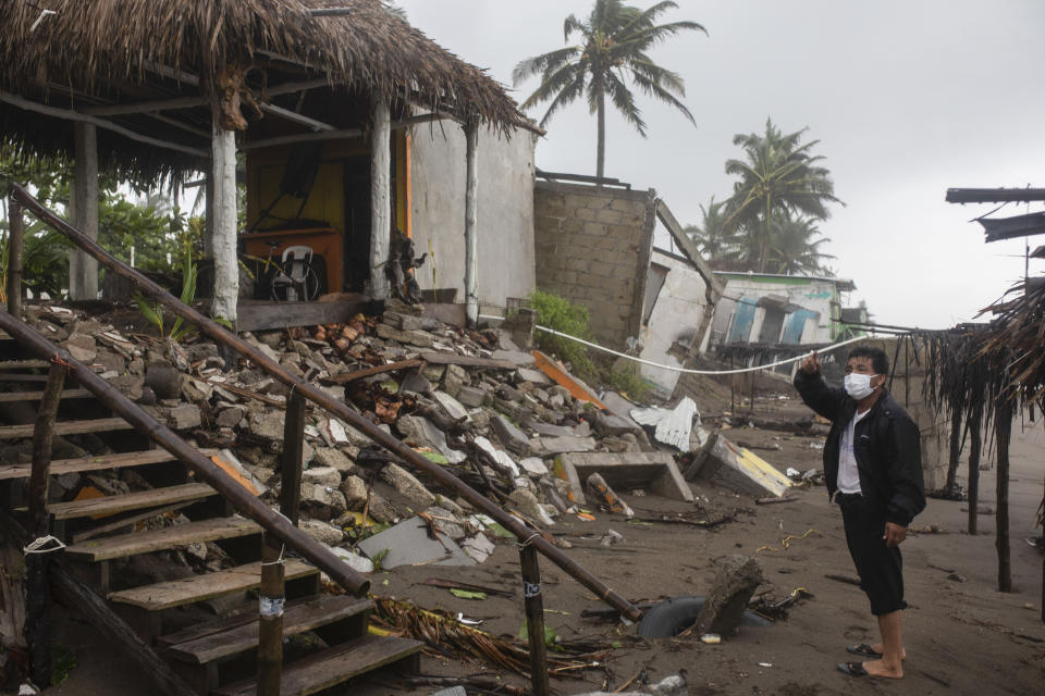 A man inspects the damage after a part of his home was toppled by winds brought on by Hurricane Grace, in Tecolutla, Veracruz State, Mexico, Saturday, Aug. 21, 2021. Grace hit Mexico's Gulf shore as a major Category 3 storm before weakening on Saturday, drenching coastal and inland areas in its second landfall in the country in two days. (AP Photo/Felix Marquez)