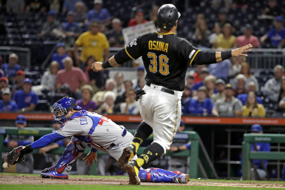 Chicago Cubs catcher Willson Contreras, left, can't glove the relay throw as Pittsburgh Pirates' Jose Osuna (36) scores on a double by Erik Gonzalez off Cubs starting pitcher Jon Lester during the fourth inning of a baseball game in Pittsburgh, Wednesday, Sept. 25, 2019. (AP Photo/Gene J. Puskar)