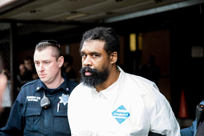 Ramapo police officers escort Grafton Thomas from Ramapo Town Hall to a police vehicle on Sunday. Thomas is accused of stabbing multiple people as they gathered to celebrate Hanukkah at a rabbi's home. (Photo: ASSOCIATED PRESS)