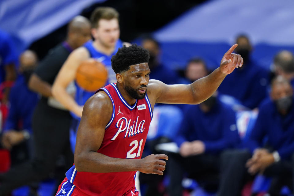 Philadelphia 76ers' Joel Embiid, right, reacts after a dunk during the first half of an NBA basketball game against the Dallas Mavericks, Thursday, Feb. 25, 2021, in Philadelphia. (AP Photo/Matt Slocum)