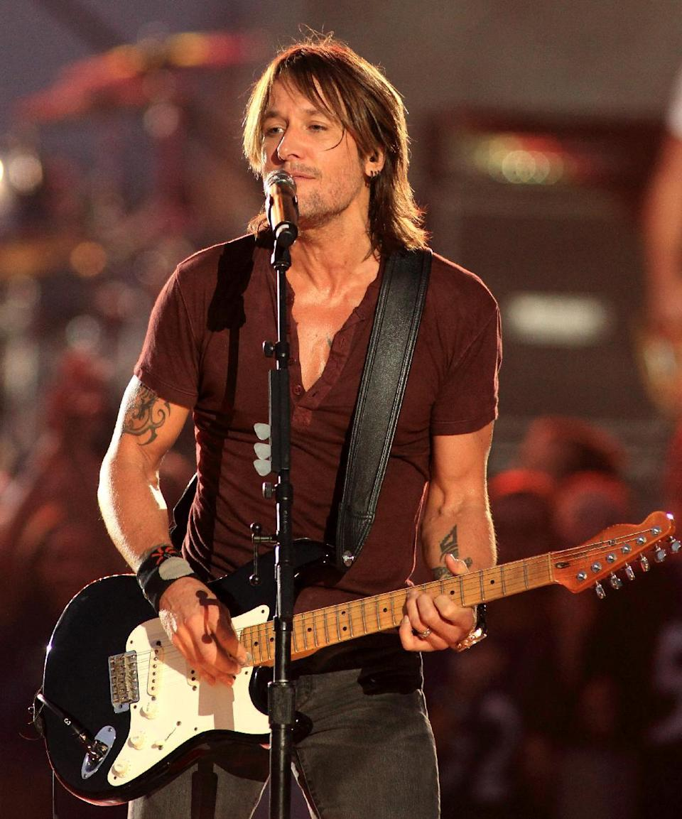 """FILE - In this Sept. 5, 2013 file photo, country music artist Keith Urban performs in concert during the NFL football Kickoff 2013 at the Inner Harbor in Baltimore. Lorde joins Macklemore & Ryan Lewis for """"The Grammy Nominations Concert Live!! _ Countdown to Music's Biggest Night,"""" to be held on Dec. 6, 2013, at the Nokia Theatre L.A. Live. Urban will take the stage with R&B singer Miguel to sing Bill Withers' """"Ain't No Sunshine."""" (Photo by Owen Sweeney/Invision/AP, File)"""