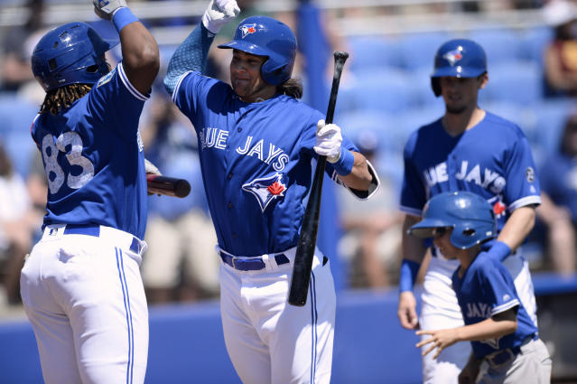 Toronto Blue Jays Vladimir Guerrero Jr., left, and Bo Bichette, right, celebrate after Bichette's two-run home run during the first inning of a spring training baseball game against the Canada Junior National Team Saturday, March 17, 2018, in Dunedin, Fla. (AP Photo/Jason Behnken)