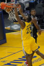 Golden State Warriors forward Andrew Wiggins (22) dunks against Sacramento Kings forward Harrison Barnes during the first half of an NBA basketball game in San Francisco, Monday, Jan. 4, 2021. (AP Photo/Jeff Chiu)