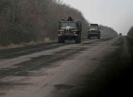 Ukrainian servicemen ride on an armoured vehicle near Debaltseve, eastern Ukraine, February 8, 2015. REUTERS/Gleb Garanich