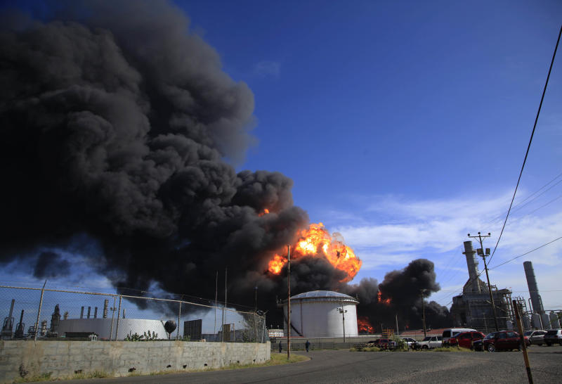 Plumes of black smoke and flames continue to rise over the Amuay refinery near Punto Fijo, Venezuela, Monday, Aug. 27, 2012. A huge explosion rocked Venezuela's biggest oil refinery, killing at least 24 people and injuring dozens, an official said. (AP Photo/Ariana Cubillos)