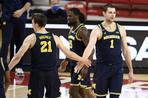 Michigan center Hunter Dickinson (1) and guard Franz Wagner (21) react during the second half of an NCAA college basketball game against Maryland, Thursday, Dec. 31, 2020, in College Park, Md. Michigan won 84-73. (AP Photo/Nick Wass)