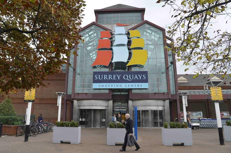 Pedestrians walk past the main entrance to the Surrey Quays shopping centre in south London
