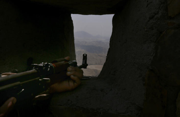 A Pakistan Army soldier observes the area from hilltop post on the Pakistan Afghanistan, in Khyber district, Pakistan, Tuesday, Aug. 3, 2021. Pakistan's military said it completed 90 percent of the fencing along the border with Afghanistan, vowing the remaining one of the most difficult tasks of improving the border management will be completed this summer to prevent any cross-border militant attack from both sides. (AP Photo/Anjum Naveed)
