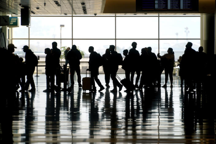 FILE - In this Wednesday, March 17, 2021 file photo, travelers walk through the Salt Lake City International Airport in Salt Lake City. On Sunday, March 21, more than 1.5 million people streamed through U.S. airport security checkpoints, the largest number since the pandemic tightened its grip on the United States more than a year ago. However, passenger traffic remains far below 2019 levels. (AP Photo/Rick Bowmer)