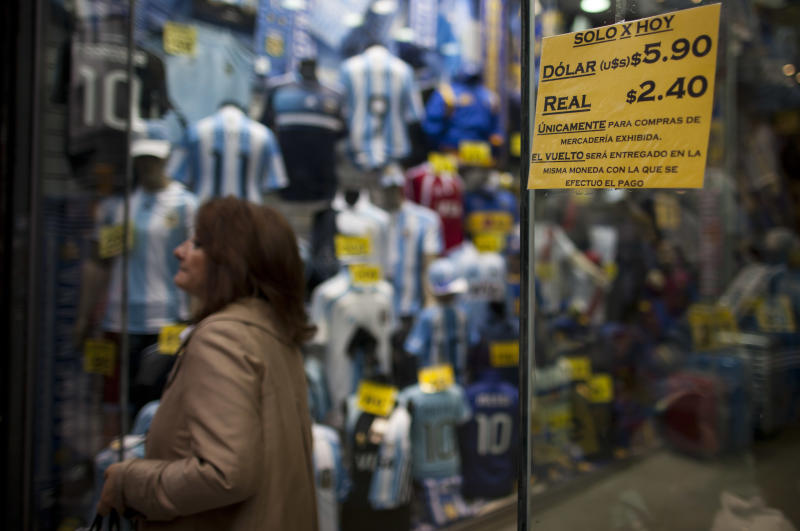 """A shop window displays a sign that reads in Spanish: """"Only for today, Dollar 5.90, Real 2.40,"""" in Buenos Aires, Argentina, Monday, May 28, 2012. Argentina is making it harder for people to buy U.S. dollars to pay for travel abroad. A new rule published Monday says anyone wanting to buy dollars for travel must first prove their money was obtained legally, and provide the tax agency with trip details including why, when and where they are traveling. President Cristina Fernandez is cracking down to keep hard currency from flowing out of Argentina, which needs the dollars to maintain its central bank reserves and pay debts. (AP Photo/Natacha Pisarenko)"""