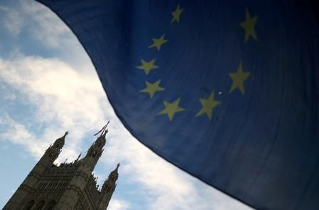 FILE PHOTO: An EU flag flutters during an anti-Brexit demonstration outside the Houses of Parliament in London